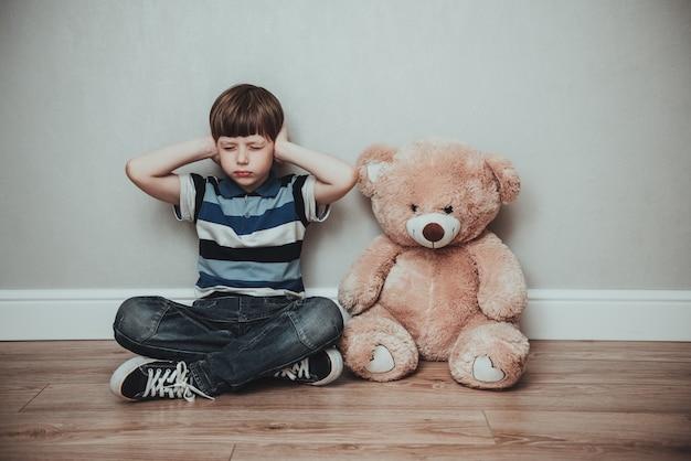 Kindjunge gegen grauen hintergrund, der ohren mit geschlossenen augenaugen bedeckt