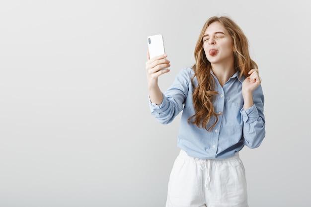 Kindliche frau, die mit liebhaber über internet spricht. sorglose attraktive europäische frau, hält smartphone, macht selfie oder video-chat, zeigt zunge auf dem bildschirm mit positiver einstellung