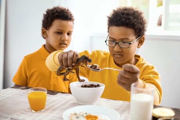 Kindliche neugier. entzückender kleiner junge, der beobachtet, wie sein jugendlicher bruder seinen spielzeugdinosaurier beim frühstück mit müsli füttert