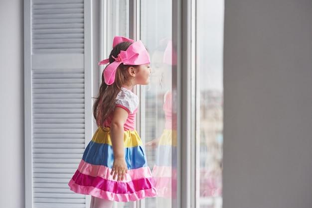 Kindliche neugier. foto des jungen niedlichen mädchens in der bunten abnutzung, die nahe am fenster steht und draußen schaut.