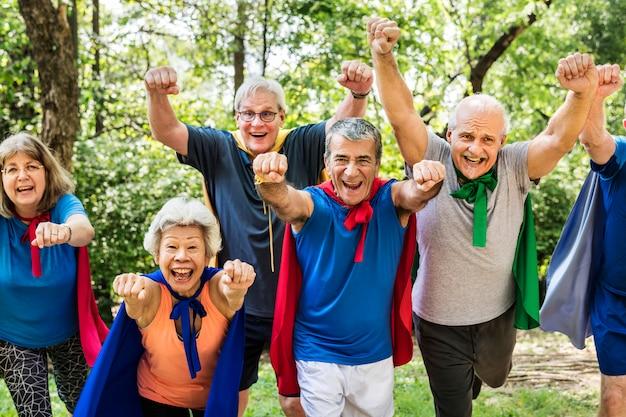 Kindliche senioren, die superheldenkostüme tragen