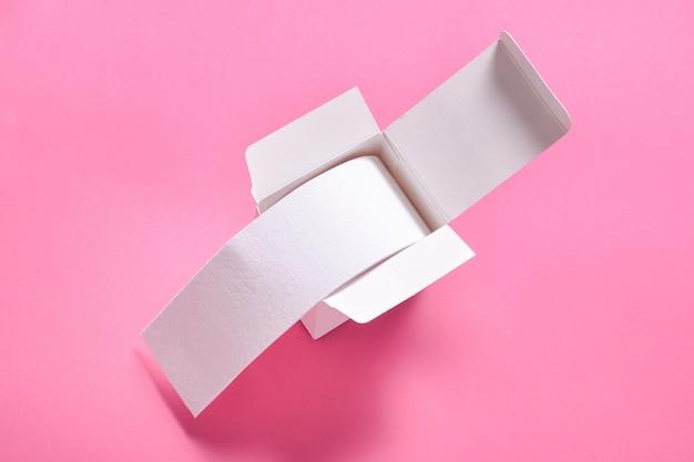 Kinesiologie-bandrolle in der weißen kartonschachtel auf rosa hintergrund