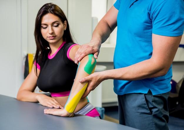 Kinesiotaping. physiotherapeut, der klebeband auf wirbelsäule, hand und elle der jungen schönen frau anbringt.