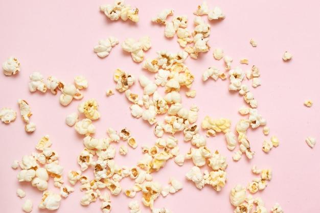 Kino, filme und unterhaltungskonzept. draufsicht des geschmackvollen popcornmusters auf rosa hintergrund.