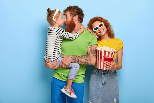 Kino ist ein beliebtes mittel der massenmedien. junge familie genießen lieblingsbeschäftigung