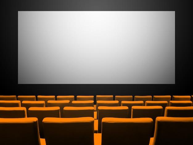 Kino kino mit orangefarbenen samtsitzen und einem leeren weißen bildschirm