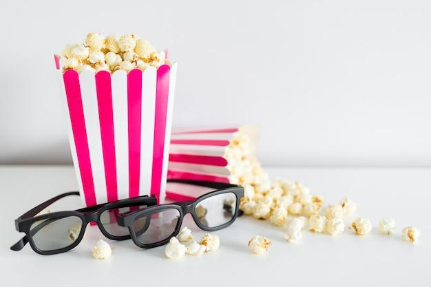 Kino- und datumskonzept schließen oben von zwei gestreiften kisten mit popcorn und gläsern