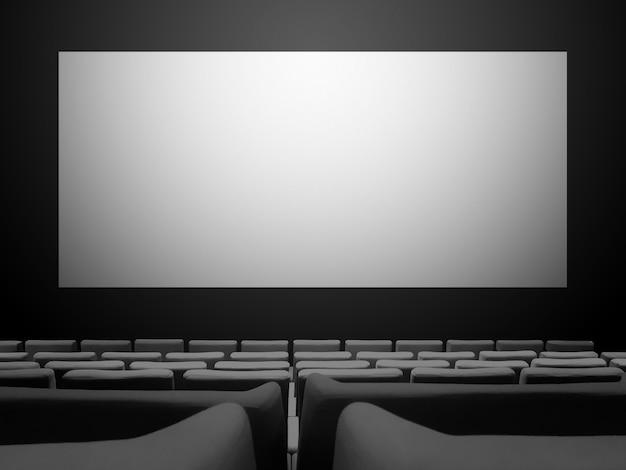Kinokino mit samtsitzen und einem leeren weißen bildschirm. raumhintergrund kopieren