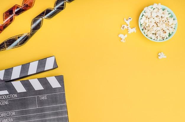 Kinokonzept - filmklappe mit popcorn und filmstreifen auf gelbem hintergrund mit kopierraum.