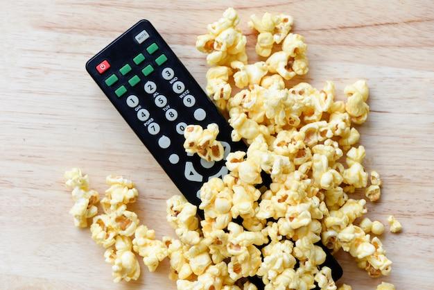Kinokonzeptpopcorn und -fernbedienung auf draufsicht des holztischs backgroubd / süßes butterpopcornsalz