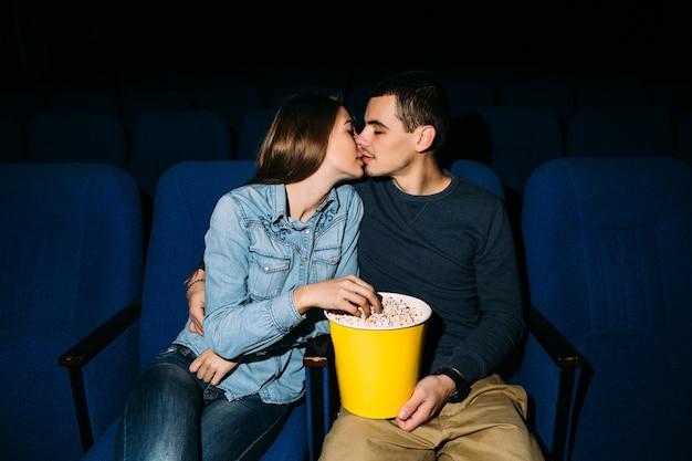Kinotag. junge schöne küssende paare beim aufpassen des romantischen films am kino.