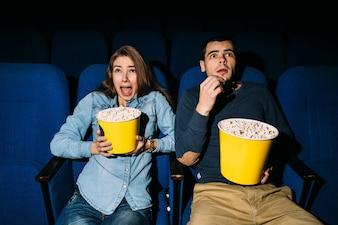 Kinotag, junges Paar mit dem Popcorn, das Horrorfilm im Kino an ihrem Datum schaut.