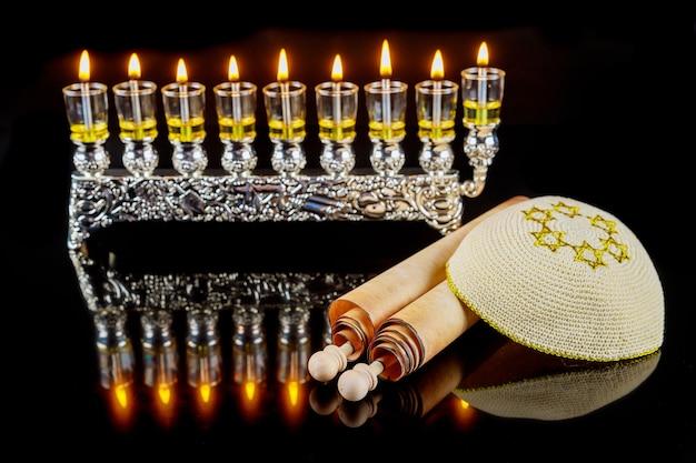 Kippah und totah für chanukka auf menora mit brennendem ölkerzenhintergrund. jüdischer feiertag.