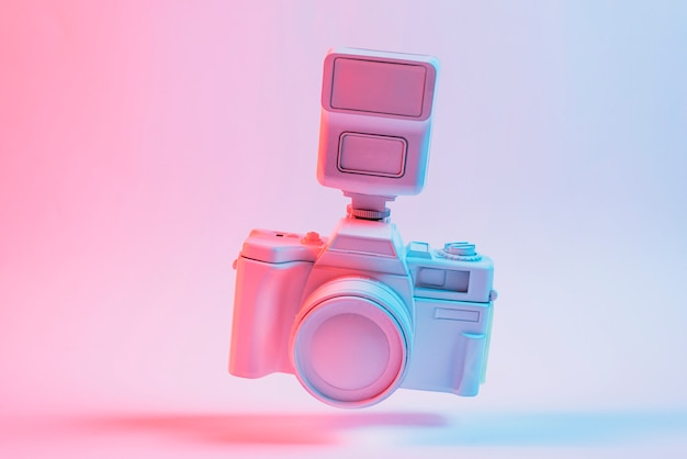 Kippen sie die kamera, die über dem rosa hintergrund schwimmt