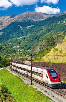 Kippender hochgeschwindigkeitszug auf der gotthardbahn in den schweizer alpen
