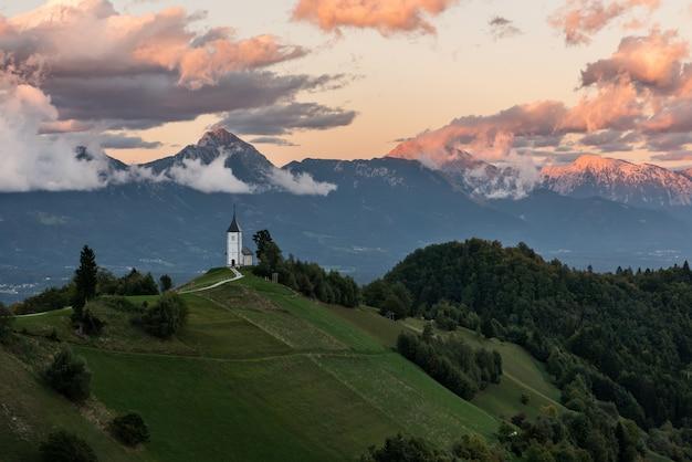 Kirche auf dem hügel bei sonnenaufgang. schöne landschaft bei kamnik, slowenien.
