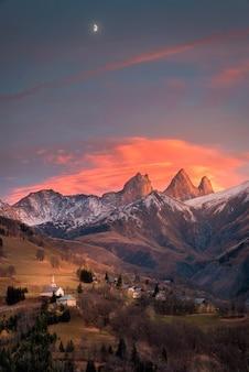 Kirche und mond in den bergen der französischen alpen gezeigt.