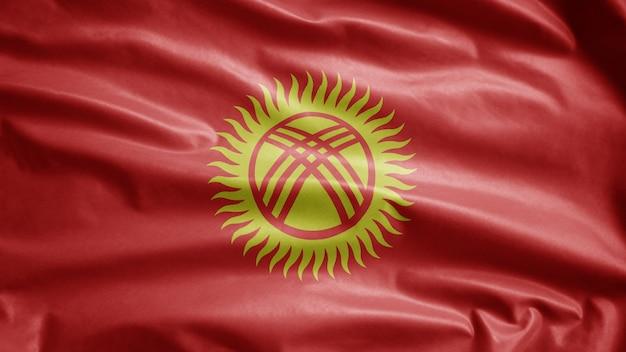 Kirgisische flagge weht im wind. nahaufnahme von kirgisistan banner weht, weiche und glatte seide. stoff textur fähnrich hintergrund. verwenden sie es für das konzept für nationalfeiertage und länderanlässe.