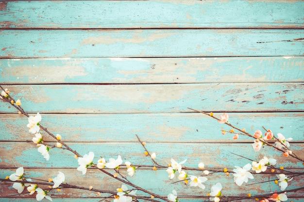 Kirschblüte blüht auf hölzernem hintergrund der weinlese, grenzdesign. weinlesefarbton - konzeptblume des frühlings- oder sommerhintergrundes