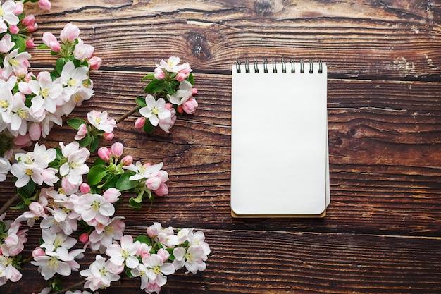 Kirschblüte-blüten auf dunklem rustikalem hölzernem hintergrund mit einem notizbuch. frühlingshintergrund mit blühenden aprikosenniederlassungen und kirschniederlassungen