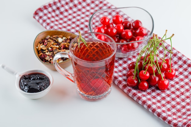 Kirsche in einer schüssel mit tee, marmelade, getrockneten kräutern high angle view auf weiß und küchentuch