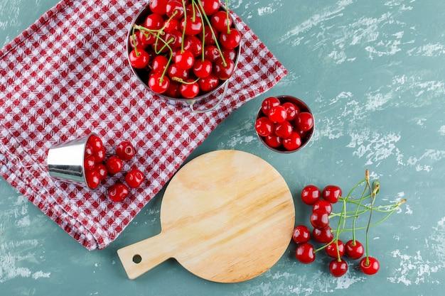 Kirsche mit schneidebrett in eimern auf gips und küchentuch, draufsicht.