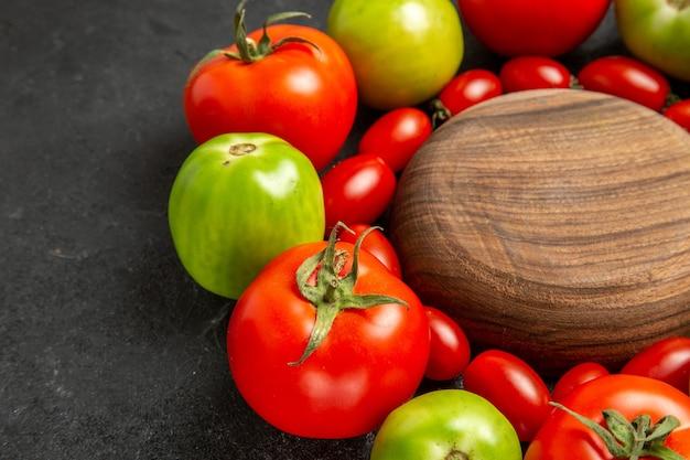 Kirsche rote und grüne tomaten der unteren nahansicht um eine hölzerne platte auf dunklem hintergrund