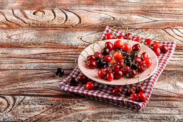 Kirschen in einer platten-hochwinkelansicht auf holz- und picknicktuchoberfläche