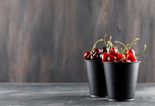 Kirschen in mini-eimern seitenansicht auf grunge und grauer oberfläche