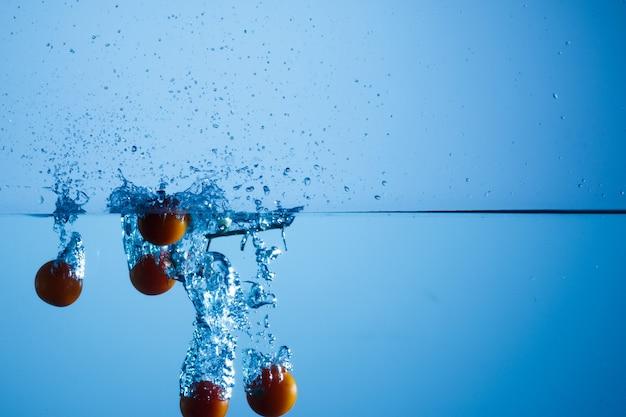 Kirschen in wasserbehälter geworfen und mit hoher geschwindigkeit fotografiert
