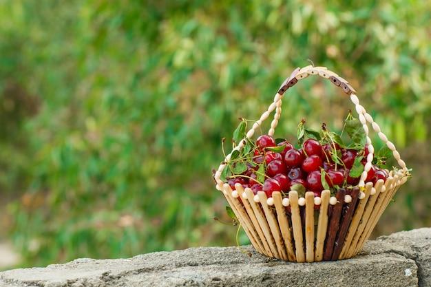 Kirschen mit blättern in einem korb auf stein- und gartenhintergrund, seitenansicht.