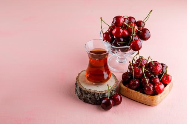 Kirschen mit glas tee auf holzbrett in holzteller und vase auf rosa oberfläche