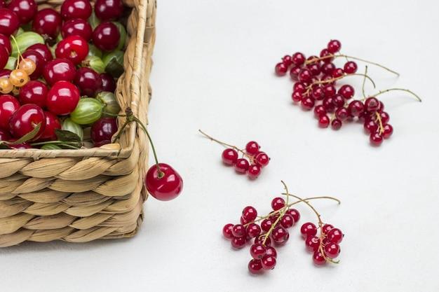 Kirschen, stachelbeeren, johannisbeeren im weidenkorb. rote johannisbeere auf dem tisch. weißer hintergrund. ansicht von oben