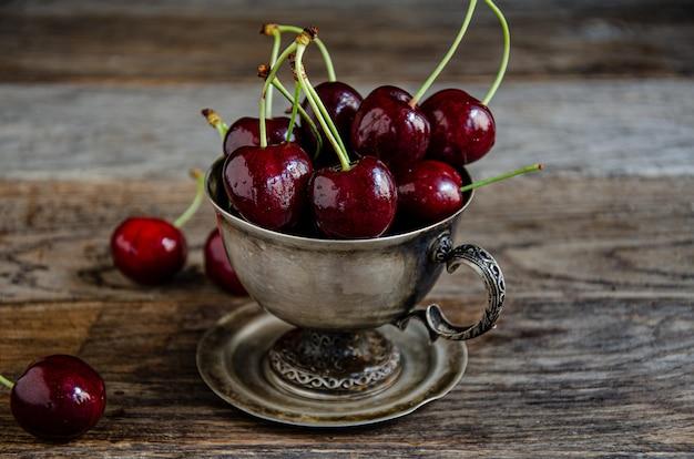 Kirschfrüchte in einer silbernen tasse und auf holzbrettern.