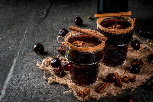 Kirschheiße sangria mit zimt, anis, wein und gewürzen auf einem dunklen und hölzernen steinhintergrund