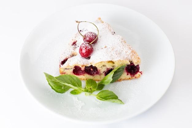Kirschkuchenscheibe von oben aus der nähe köstlich und lecker in weißer platte auf dem weißen hintergrundkuchenkeks süßer zuckerteig backen