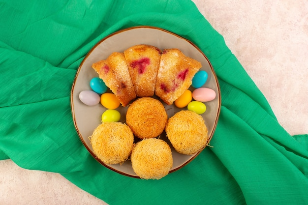 Kirschkuchenscheiben von oben mit süßigkeiten und keksen auf dem rosa schreibtischkuchenkeks süß