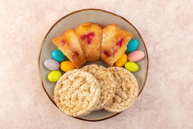 Kirschkuchenstücke von oben mit süßigkeiten und keksen auf dem rosa schreibtischkuchenkekszuckersüß