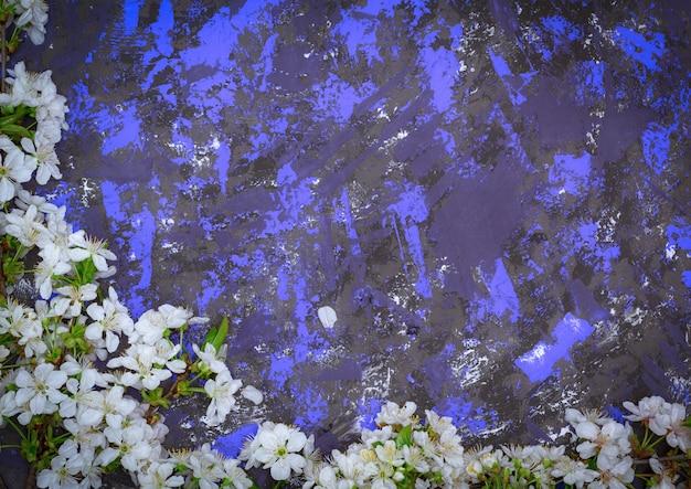 Kirschniederlassungen mit den weißen blühenden knospen auf einer strukturierten oberfläche