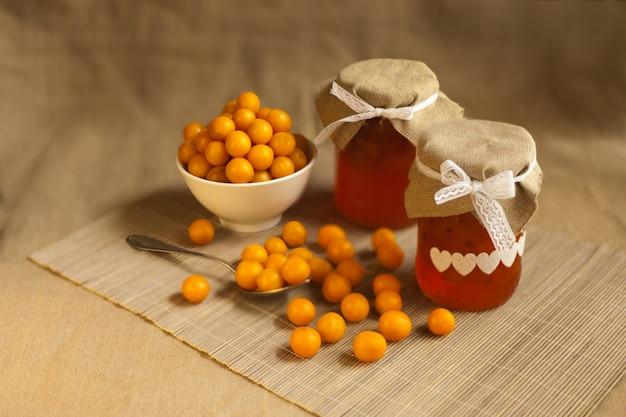 Kirschpflaumen gelbe marmelade, frische beerenfrüchte. hausgemachte marmelade im glas auf braunem textilhintergrund