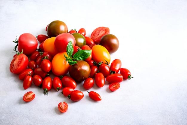 Kirschtomate auf grauem hintergrund mit copyspace. rote, gelbe und schwarze tomaten, basilikumblätter.