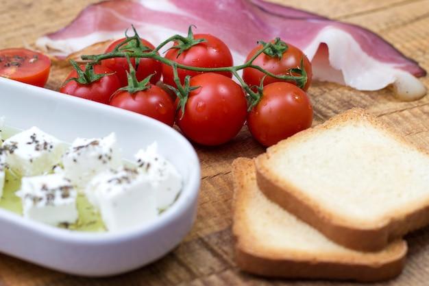 Kirschtomate, käse und prosciutto mit toast auf holztisch