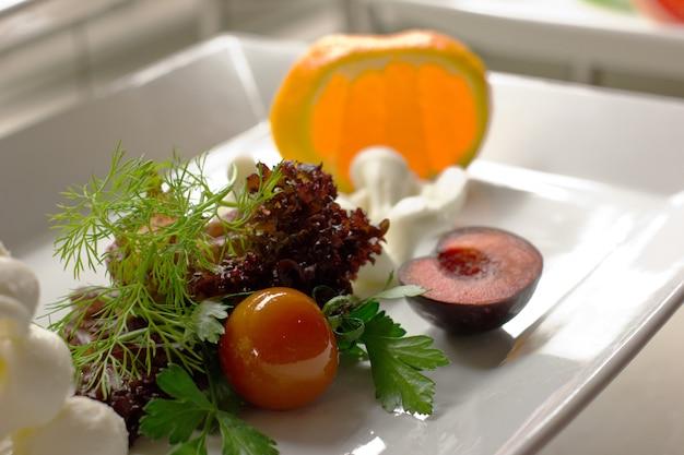 Kirschtomate mit salat, dill, weißkäse und orange auf einem teller