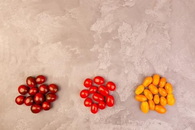 Kirschtomaten auf grauem marmorhintergrund. copyspace.