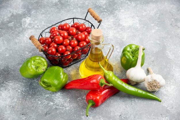 Kirschtomaten im korb mit chilischoten, knoblauch und olivenöl.