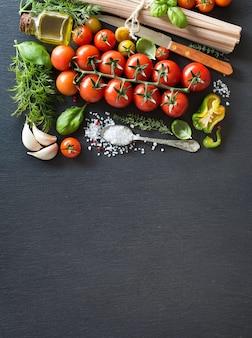 Kirschtomaten, kräuter, nudeln und olivenöl auf einem dunklen brett mit kopierraum