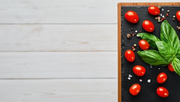 Kirschtomaten mit basilikumblättern, salz und pfeffer, layout auf einem schwarzen steinbrett. zutaten für die herstellung von caprese-salat. kopieren sie raum auf weißem hölzernem hintergrund, draufsicht