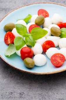 Kirschtomaten, mozzarella, basilikum und gewürze auf grauer schiefersteintafel. italienische traditionelle caprese-salatzutaten. mediterranes essen.