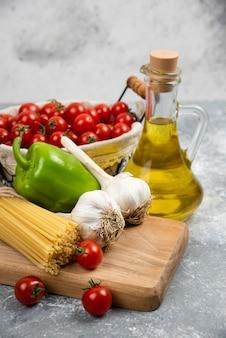 Kirschtomaten, nudeln, knoblauch, grüner pfeffer und olivenöl auf einem holzbrett.