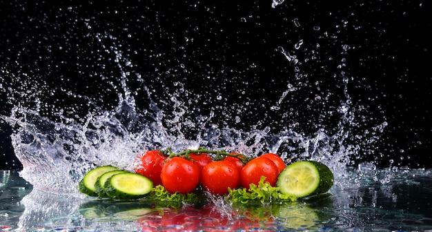 Kirschtomaten und gurkenscheiben im wasserspritzer